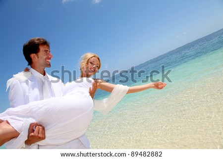 Groom holding bride in his arms by the sea - stock photo