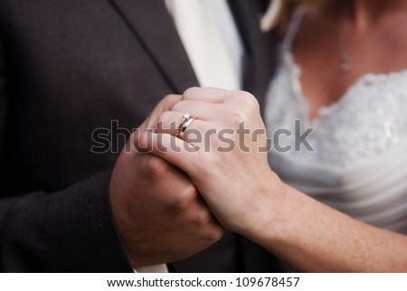 Groom holding brides hands in unity. - stock photo