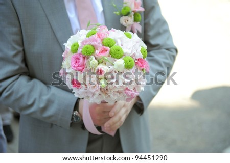Groom holding elegant wedding bouquet in hand - stock photo