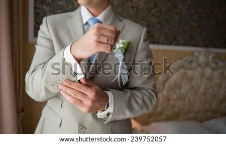groom in a suit, hands wear cufflinks. - stock photo