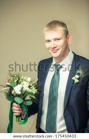 Groom is holding a flower's bouquet and smiling. - stock photo