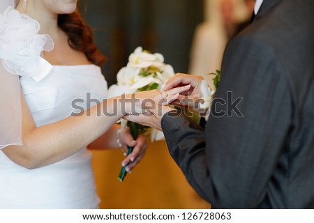 Groom is putting the ring on bride's finger - stock photo