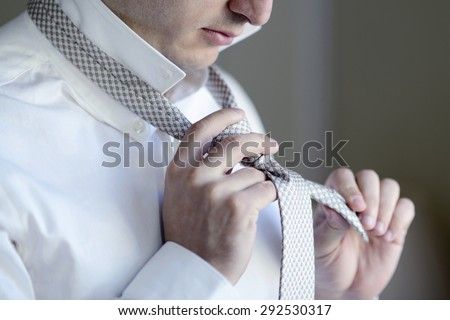 Groom is wearing a tie indoors. Male portrait of handsome guy. Beautiful model boy in colorful wedding clothes. Man is posing - stock photo