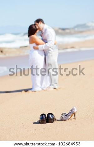 groom kissing bride on beach - stock photo