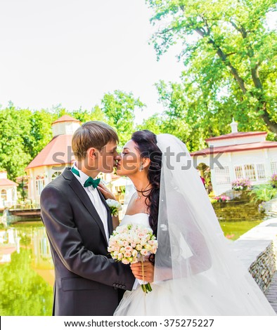 Groom kissing bride on their wedding day - stock photo