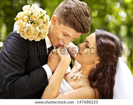 Groom kissing bride outdoor. - stock photo