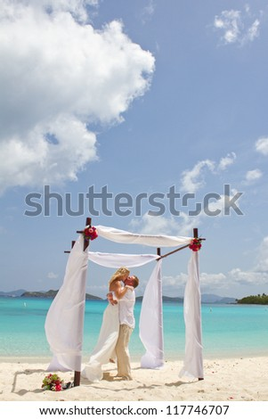 Groom Kissing Bride Under Beautiful Beach Altar - stock photo