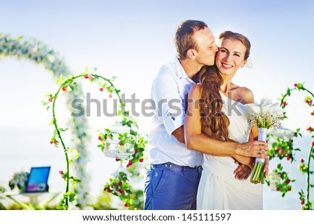 groom kissing his bride on wedding day near floral arch on wedding venue - stock photo