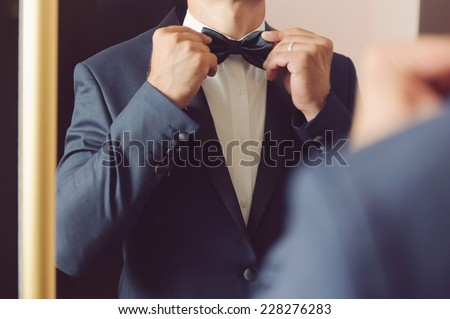 groom looking in mirror and touching bowtie - stock photo