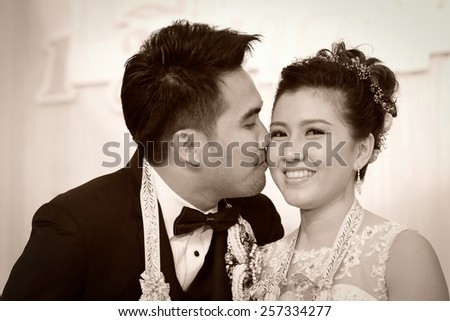 groom lovingly kissing his biracial bride on her cheek ,thai wedding culture - stock photo