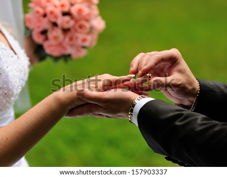 Groom put a ring on finger of his lovely wife. Wedding couple together. - stock photo
