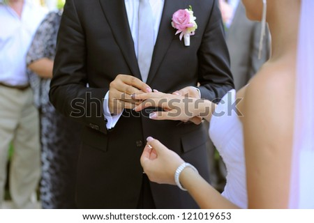 groom puts wedding ring on bride's finger - stock photo