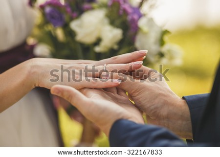 Groom putting a wedding ring on bride's finger. - stock photo