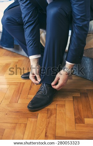 Groom putting his wedding shoes - stock photo