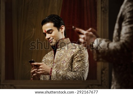 Groom reading an sms on a mobile phone - stock photo