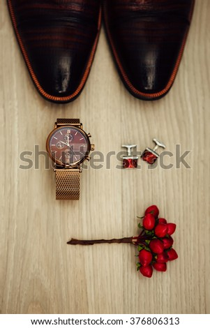 Groom's morning. Wedding accessories in red colors. Cufflinks, watch, shoes, boutonniere. - stock photo