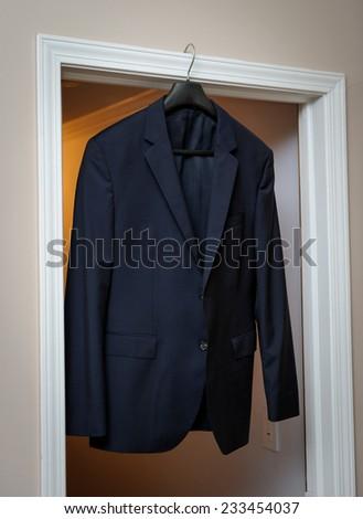Groom's suit hanging on the door frame - stock photo