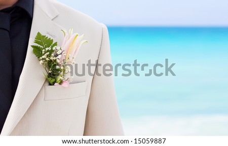 Groom's wedding suit with boutonniere made of flower and green leaves - stock photo