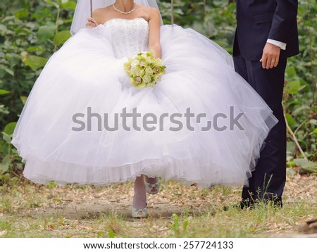 groom standing close to bride on swing - stock photo