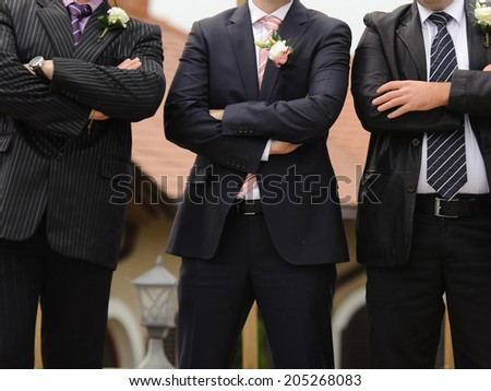 groom standing with two groomsmen in yard - stock photo