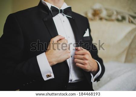groom straightens his jacket - stock photo