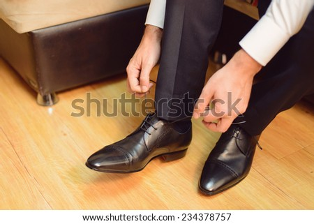 groom straining laces on wedding shoes - stock photo