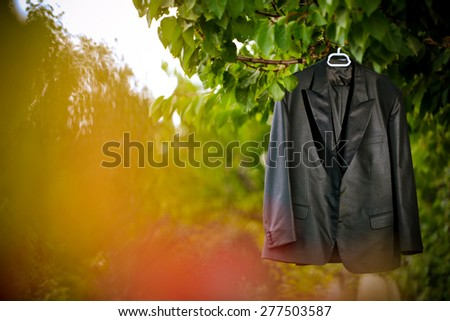 Groom suit hanging by the tree - stock photo