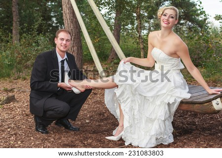 Groom takes his young bride's shoes, looking into the camera./ Groom takes his bride to the shoes. - stock photo