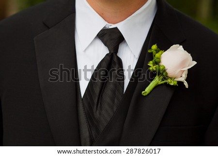 Groom wearing a boutonniere consisting of a rose and hypericum at a wedding.   - stock photo