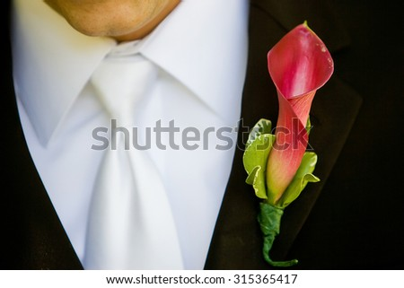 Groom wearing a red and green boutonniere - stock photo