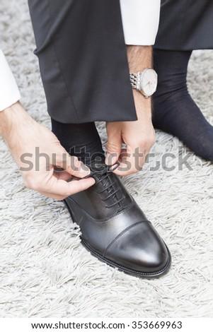groom wears his black shoes - stock photo