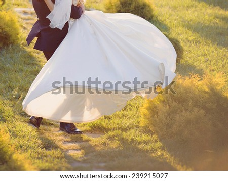 groom whirling bride at sunset light - stock photo
