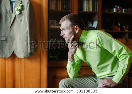 Groom with brown bow tie in green shirt - stock photo