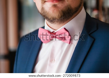 Groom with pink bowtie and beard - stock photo