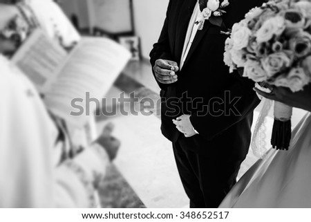 Groom with ring in his hand and the bride with luxury bouquet of roses on their wedding ceremony in front of a priest, who crowned them. - stock photo