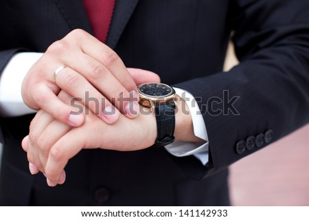 Groom with the clock on the hand - stock photo