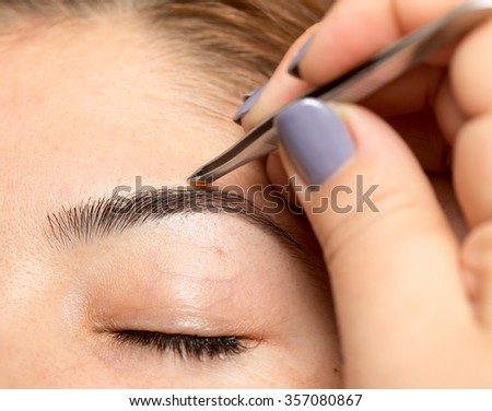 Grooming the eyebrows in a beauty salon - stock photo