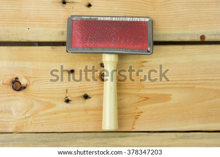 Grooming tools. Close up on brush on wooden background - stock photo
