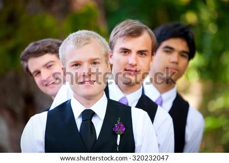 Groomsmen peeking from behind smiling groom, outdoor - stock photo