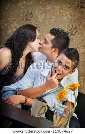 Grossed out child in front of kissing parents - stock photo