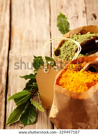 Ground Asian spices in paper bags with matcha green tea powder and turmeric, cayenne or curry powder on a rustic wooden table with copyspace, close up high angle view with a blank gift tag - stock photo