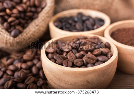 Ground coffee and coffee beans in the wood bowls, background is the coffee bags on the wooden table - stock photo