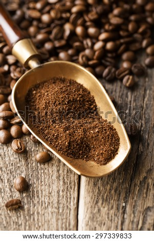 ground coffee in scoop and coffee beans on a wooden background, view from the top - stock photo