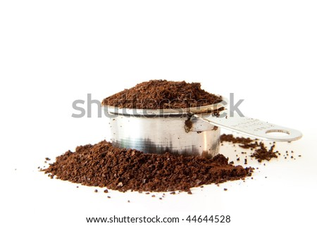 Ground coffee spilling out of a full coffee measure. Shot on white background. Focus is on the edge of the cup. Coffee in the foreground is out of focus. - stock photo