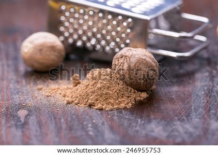 Ground nutmeg spice on the wooden background - stock photo