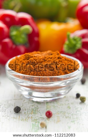 Ground paprika in a glass bowl and fresh pepper - stock photo