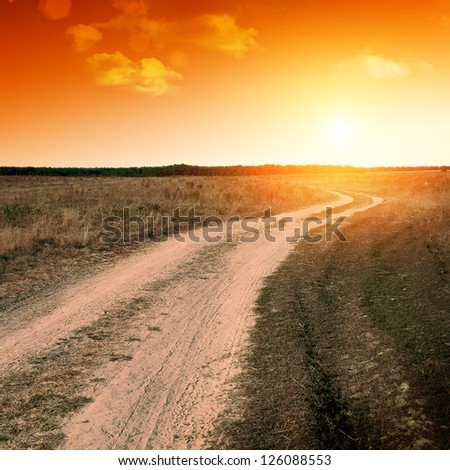 ground road in the field at sunset - stock photo