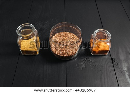 Ground spices in bottles with grain flax in glass plate on black wooden background.  - stock photo