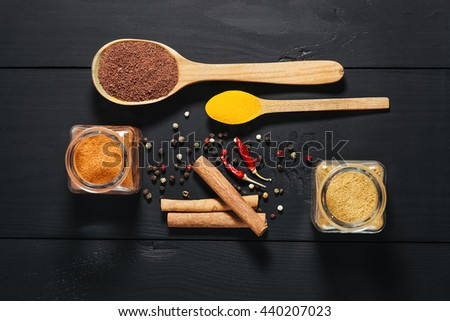 Ground spices in bottles with spoon, pepper, cinnamon on black wooden background. Close-up - stock photo