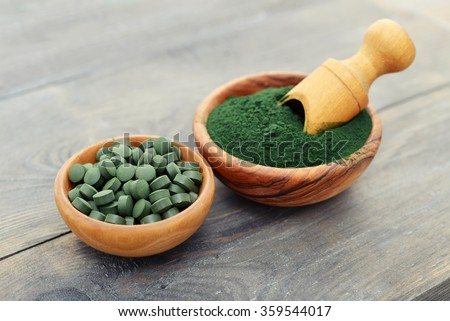 Ground spirulina and spirulina in pills over black wooden background - stock photo